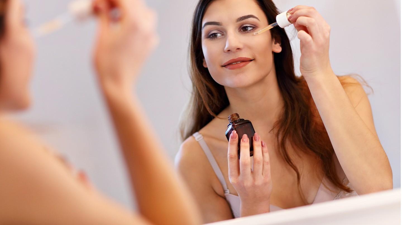 Seren und ihre konzentrierten Wirkstoffe pushen die Gesichtshaut der Frau, die in den Spiegel schaut.in Gesichts-Serum auf um Falten zu reduzieren..
