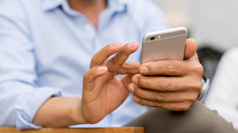 Mann in blauem Hemd tippt mit Fingern auf einem Smartphone.