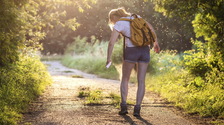 Insektenstiche: Wandererin sprüht sich die nackten Beine mit einem Insektenschutzmittel ein.